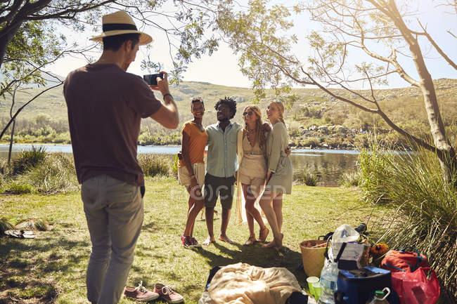 Junger Mann fotografieren Freunde am sonnigen Sommer am Fluss — Stockfoto