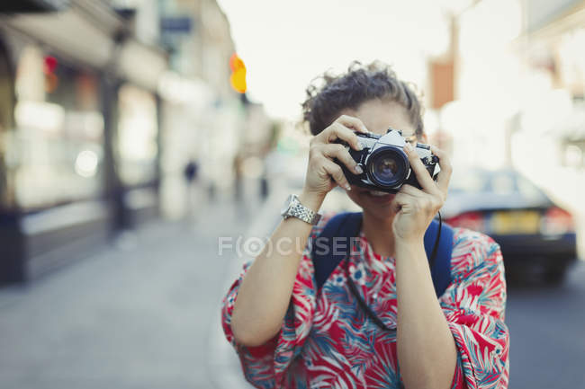 Portrait young woman photographing with camera on street — Stock Photo