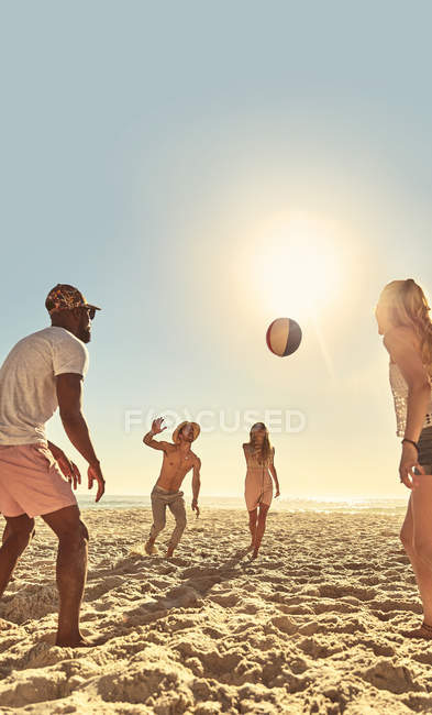 Young friends playing with beach ball on sunny summer beach — Stock Photo