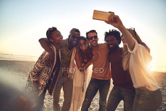 Юные друзья с камеры телефона принимая selfie на солнечный летний пляж — стоковое фото
