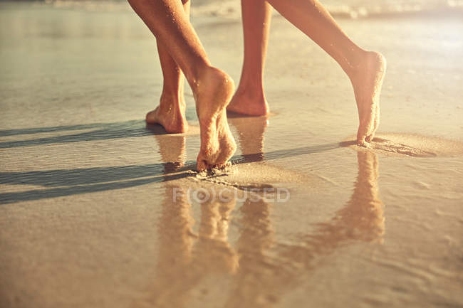 Bare feet of women walking on wet sand on sunny summer beach — Stock Photo