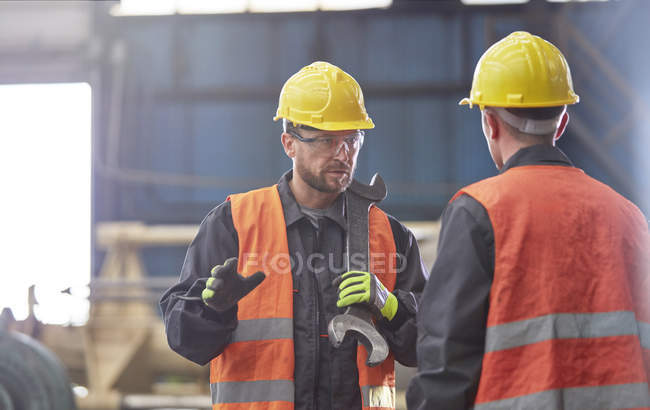 Male worker with large wrench talking to coworker in factory — Stock Photo