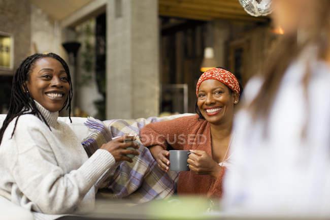Lächelnde Frauen reden und trinken Kaffee auf dem Sofa — Stockfoto