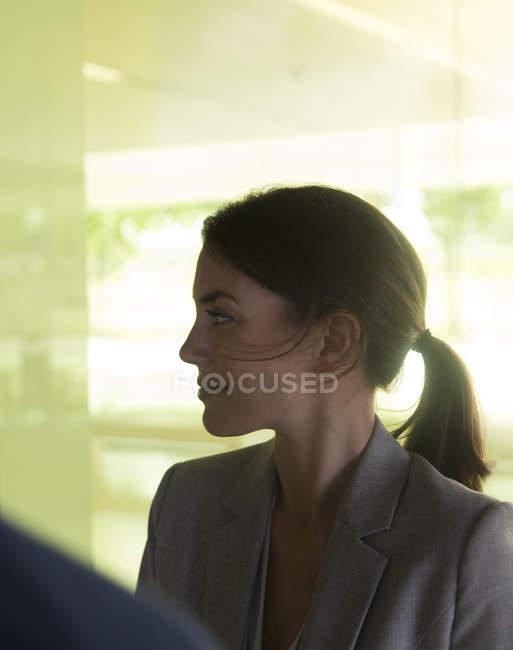 Профіль брюнетка бізнес-леді прослуховування, хтось дивитися вбік — стокове фото