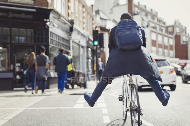 Jovem empresário brincalhão viajando, andando de bicicleta na ensolarada rua urbana — Fotografia de Stock