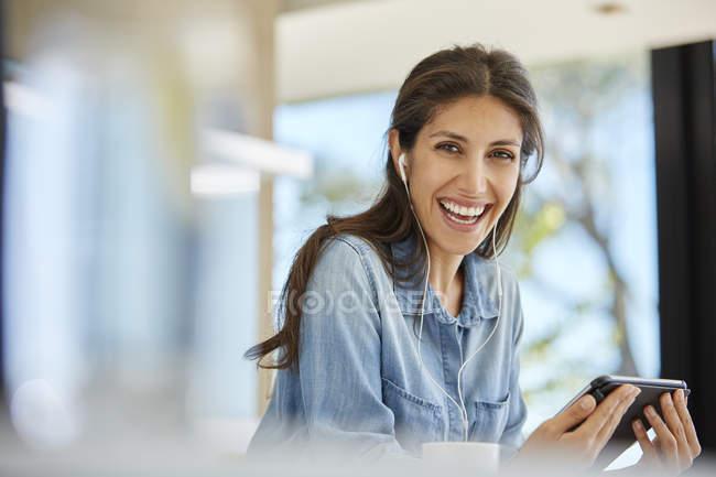 Femme enthousiaste de portrait à l'aide d'écouteurs et tablette numérique — Photo de stock