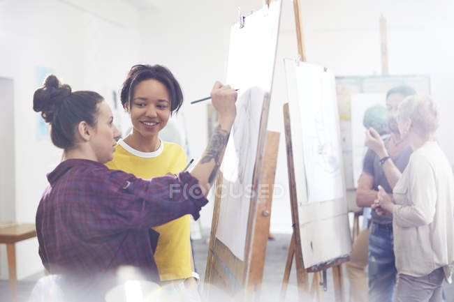 Female artists sketching at easel in art class studio — Stock Photo