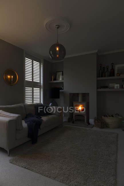 Schummriger Kronleuchter und Holzofen im Wohnzimmer — Stockfoto