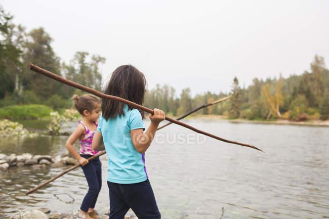 Дівчата з палички на озері риболовля — стокове фото