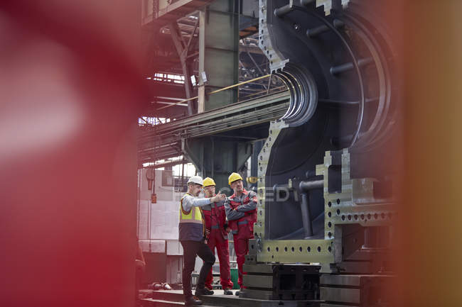 Male foreman and workers examining large steel equipment in factory — Stock Photo