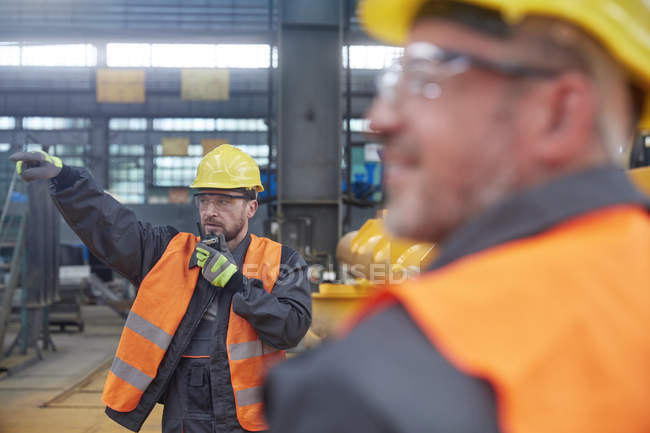 Male foreman using walkie-talkie in factory — Stock Photo