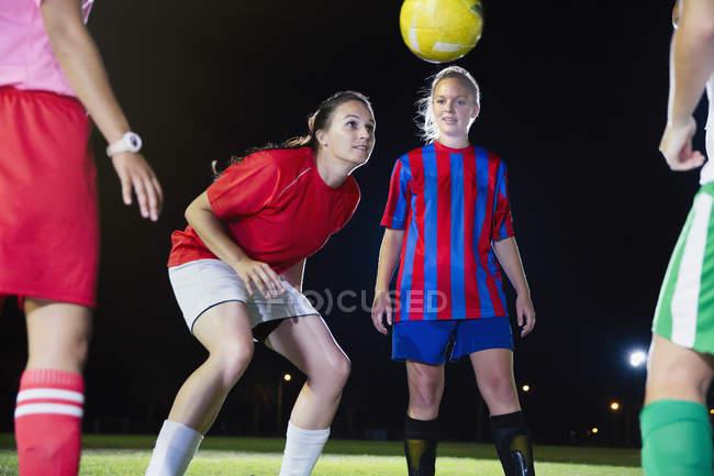 Молода жінка футболістів практикувати на поле в нічний час, статті м'яч — стокове фото