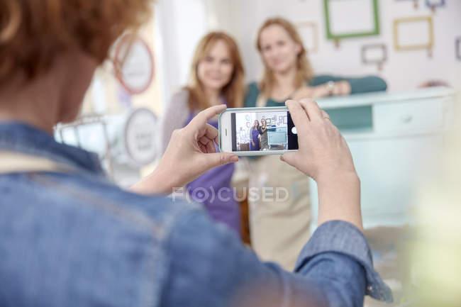 Mulher com a câmera do celular fotografando colegas posando na mesa do lado pintado na oficina de arte classe — Fotografia de Stock