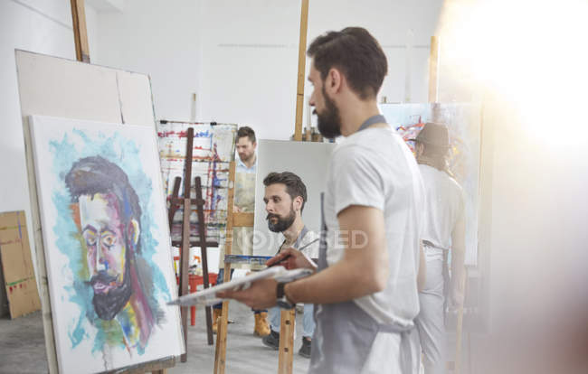 Male artists painting at easel in art class studio — Stock Photo