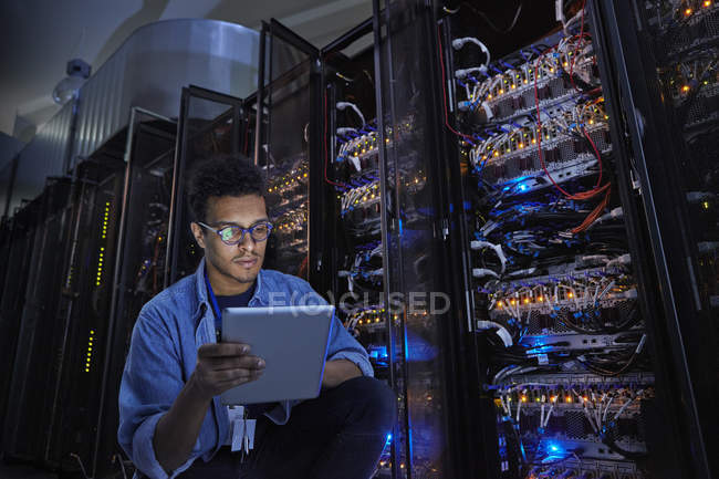 Focused male IT technician using digital tablet in dark server room — Stock Photo