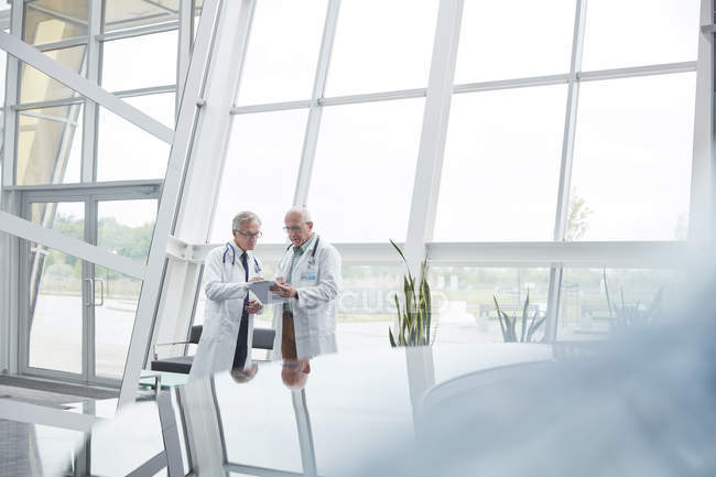 Male doctors with clipboard talking in hospital lobby — Stock Photo