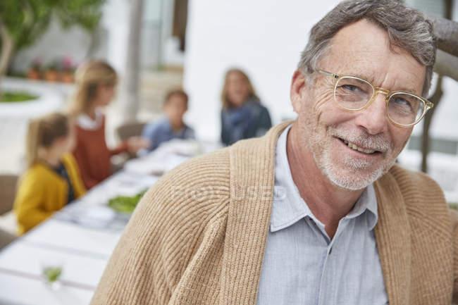 Portrait souriant senior homme appréciant déjeuner patio avec famille — Photo de stock