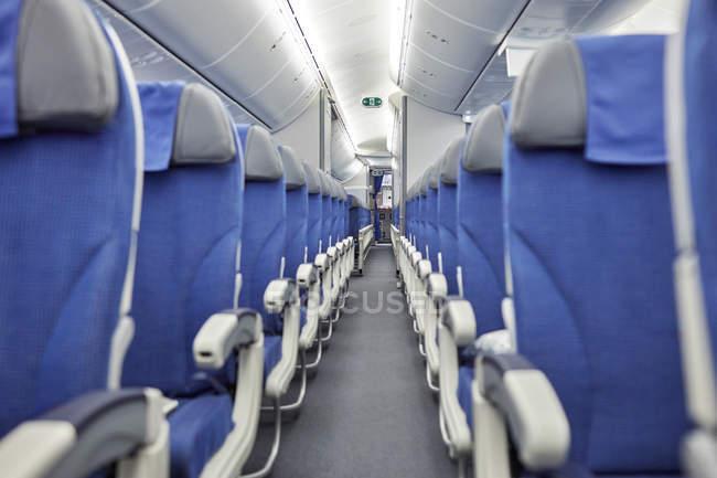 Assentos azuis vazios em uma fileira no avião — Fotografia de Stock
