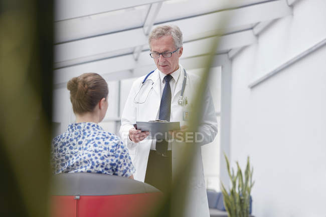 Male doctor with clipboard talking to female patient in hospital lobby — Stock Photo