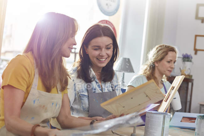 Smiling female artists painting picture frames in art class workshop — Stock Photo