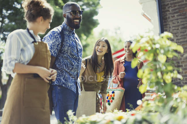 Female florist helping friends at sunny flower shop storefront — Stock Photo