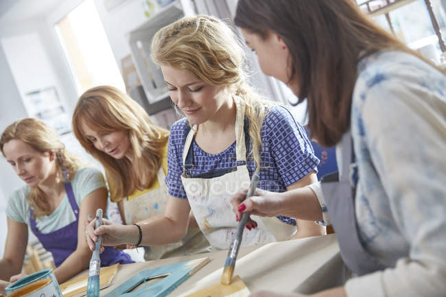 Female artists painting picture frames in art class workshop — Stock Photo