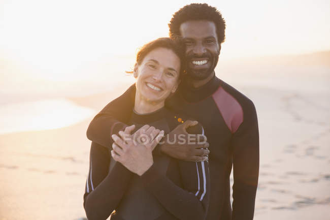 Portrait smiling, affectionate couple hugging on sunset summer beach — Stock Photo