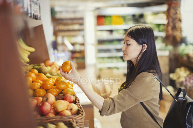 Joven mujer de compras, examen de naranjas en el supermercado - foto de stock