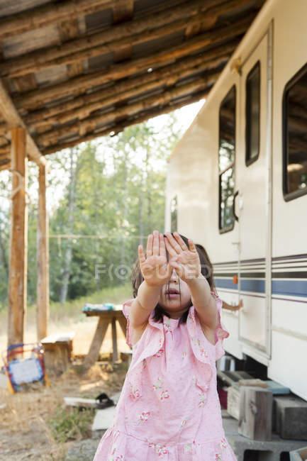 Портрет застенчивая девушка скрывает лицо с руками за пределами сельской стоянки — стоковое фото