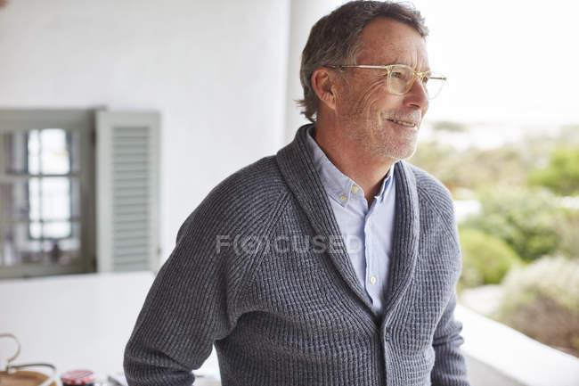 Homme senior à la recherche de suite sur patio souriant — Photo de stock