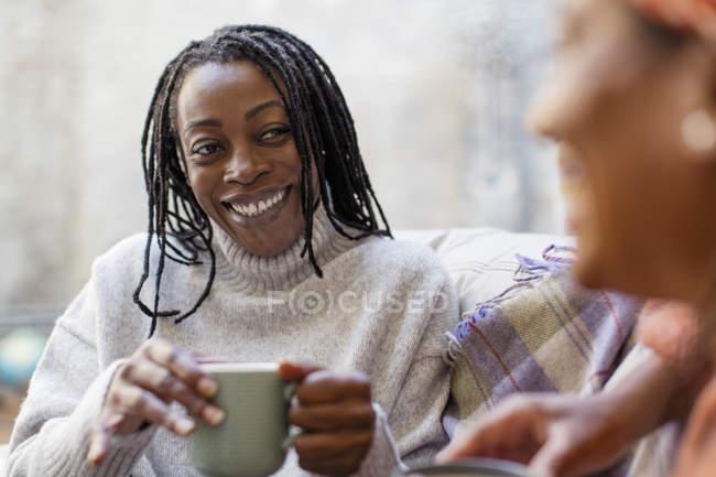 Begeisterte, lächelnde Frau hört Freundin zu und trinkt Kaffee — Stockfoto