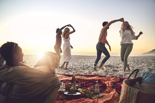 Young couples dancing, enjoying picnic on summer beach — Stock Photo