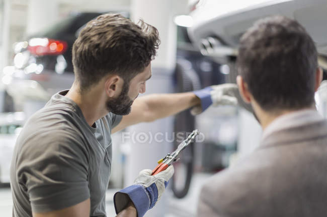 Auto mechanic with tool pointing, explaining to customer in auto repair shop — Stock Photo