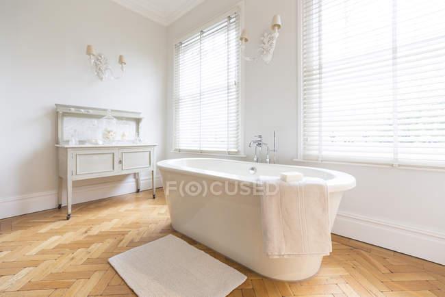 Blanc, vitrine maison intérieur salle de bain luxueuse avec une grande baignoire et parquet plancher de bois franc — Photo de stock