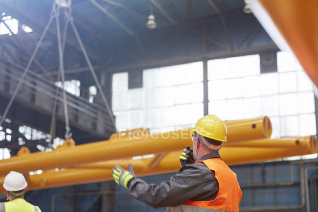 Male worker with walkie-talkie guiding lowering of equipment in factory — Stock Photo