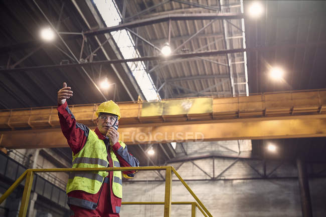 Steelworker talking, using walkie-talkie on platform in steel mill — Stock Photo