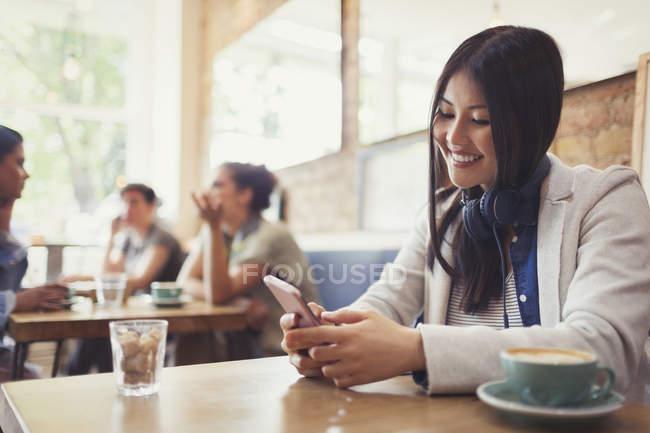 Jeune femme souriante avec écouteurs textos avec téléphone portable et boire du café à la table du café — Photo de stock