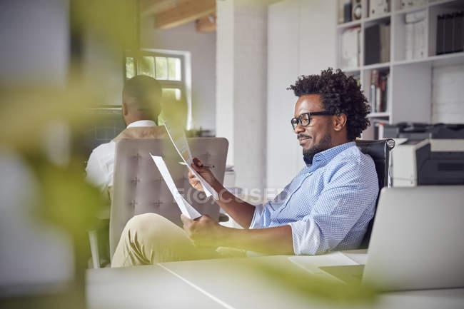 Бизнесмен читает документы в современном офисе — стоковое фото