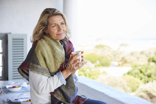 Serene woman drinking coffee on patio — Stock Photo