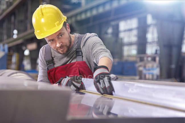 Focused male worker examining steel in factory — Stock Photo