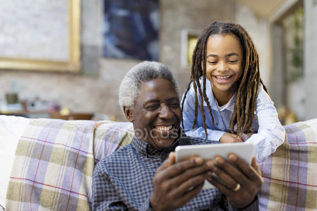 Happy grandfather and granddaughter using smart phone on sofa — Stock Photo
