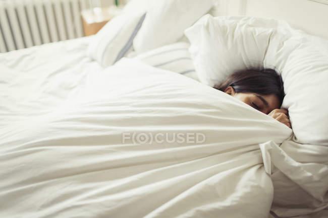 Mulher jovem cansada e dormir na cama — Fotografia de Stock