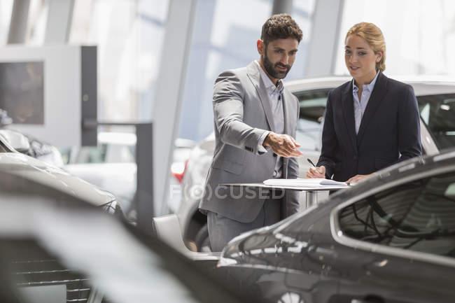 Встреча продавцов автомобилей, осмотр нового автомобиля в автосалоне — стоковое фото