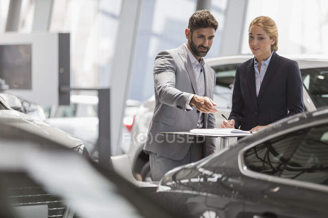 Car sales people meeting, examining new car in car dealership showroom — Stock Photo