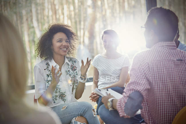 Smiling woman talking and gesturing in group therapy session — Stock Photo