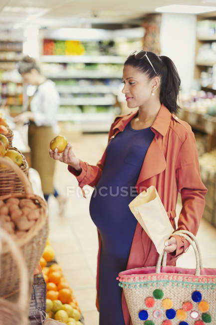 Femme enceinte shopping pour les pommes en épicerie — Photo de stock