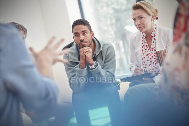 Attentive man and woman listening in group therapy session — Stock Photo