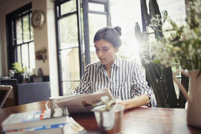 Junge Frau mit Zeitung im Esszimmer — Stockfoto