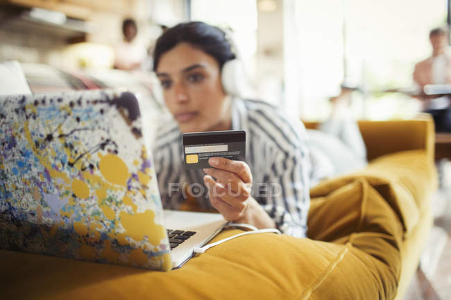 Young woman with headphones and credit card online shopping at laptop on living room sofa — Stock Photo