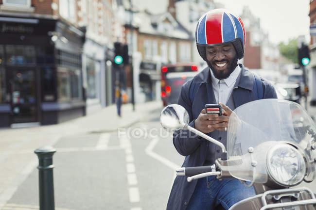 Улыбающийся молодой бизнесмен в шлеме на мотороллере смс с сотовым телефоном на городской улице — стоковое фото